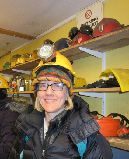 "Figure 6. The author in the ""tool room"" of former mine 3, now a tourist destination. This room includes many of the different kinds of tools Longyearbyen miners have used over the past century. All tour attendees were given hard hats with headlamps before we descended into the mine. Later, some attendees donned lompen. Photo by the author."